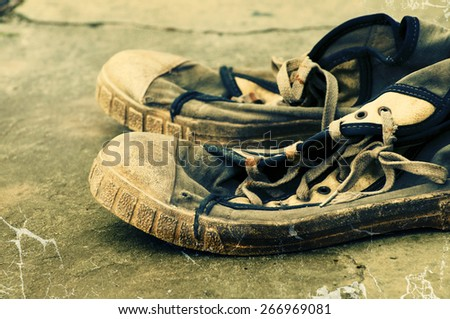 Old dirty retro gym shoes on grunge a background. Old sports shoes. Vintage sneakers.  - stock photo