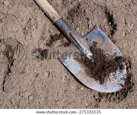 Old dirty shovel on the dry ground - stock photo