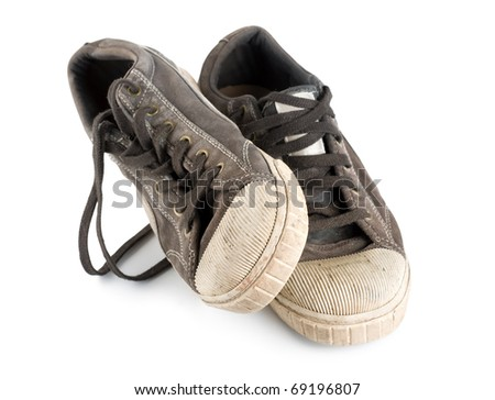 Old dirty sneakers isolated on white background