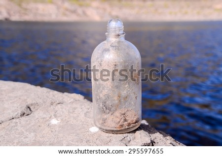 Old Dirty Vintage Gass Bottle near the Water - stock photo
