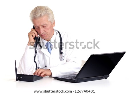 old doctor with a laptop on a white background - stock photo