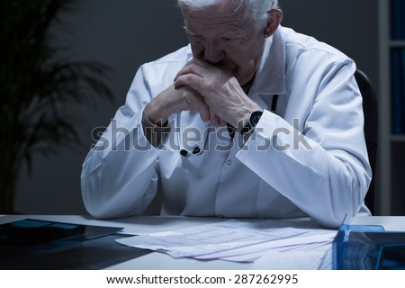 Old doctor with deep depression crying in solitude - stock photo