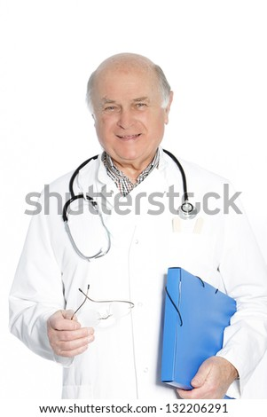 Old doctor with stethoscope wearing white gown and holding his glasses - stock photo