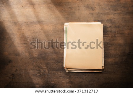 Old documents in blank on a old wooden desk, with by the window type light coming in. Ready for inserting your message or text.  - stock photo