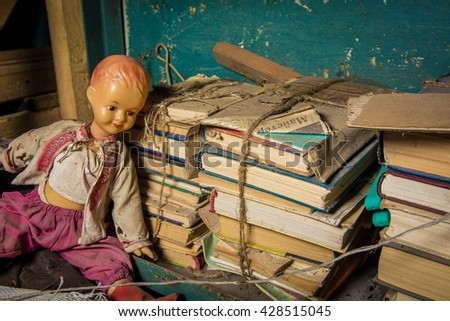 Old doll, stack of very old dusty newspapers and books in the basement - stock photo