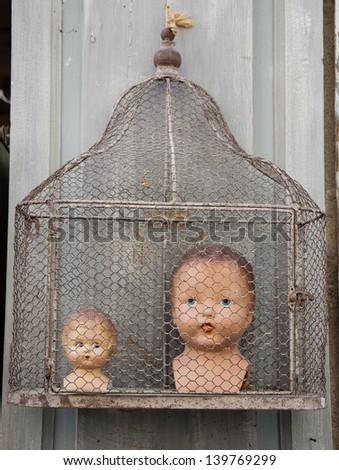 Old dolls heads in cage at flea market. - stock photo