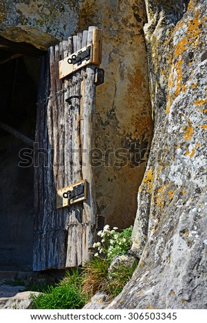 old door from logs in a cave Crimean monastery - stock photo