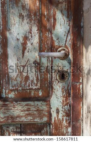 Old door handle on wooden blue textured door - stock photo