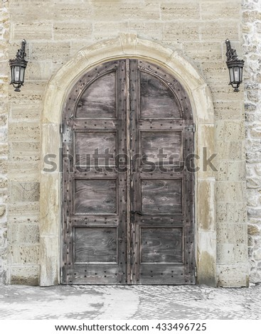Old door or gates with lamps on the wall. - stock photo
