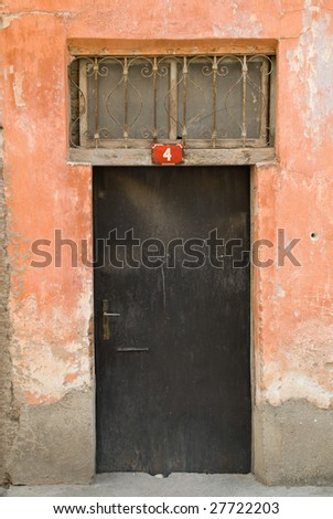 Old Door, with a weathered orange wall, with number 4. - stock photo