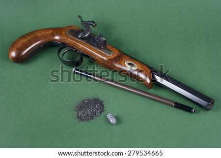 Old duel pistol with an accessory on green background - stock photo