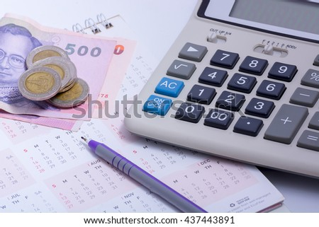 Old dusty ball pen on calculator with stack coins background - stock photo