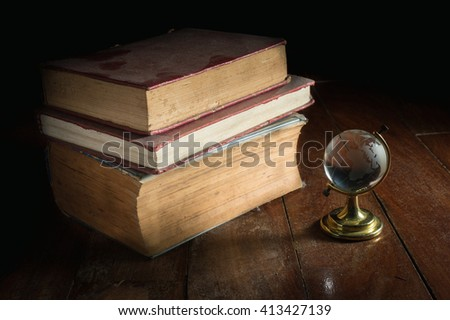 Old dusty books with glass globe. - stock photo