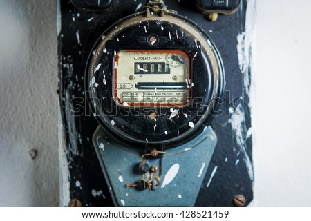 Old dusty electric meter on white wall - stock photo