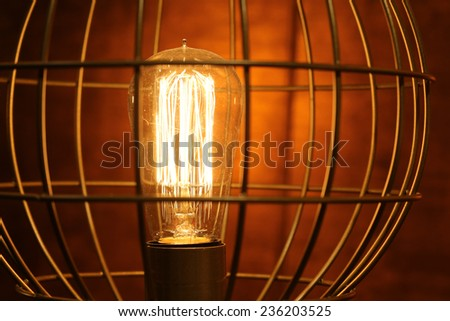 Old dusty light bulb glowing in the dark. - stock photo