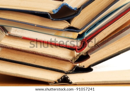 old dusty opened books stack on table - stock photo