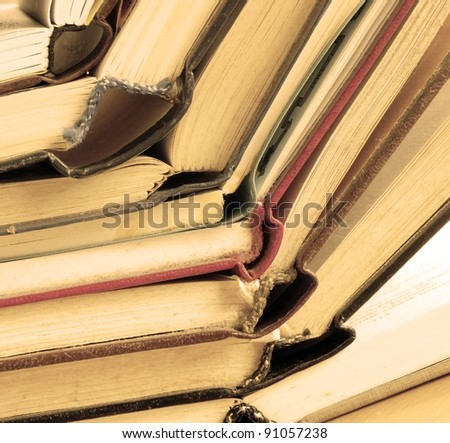 old dusty opened books stack on table, sepia toned - stock photo