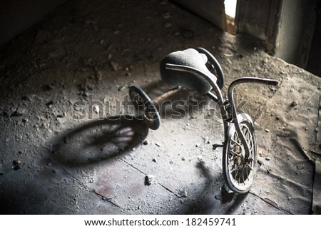 Old dusty tricycle standing on the wooden floor - stock photo