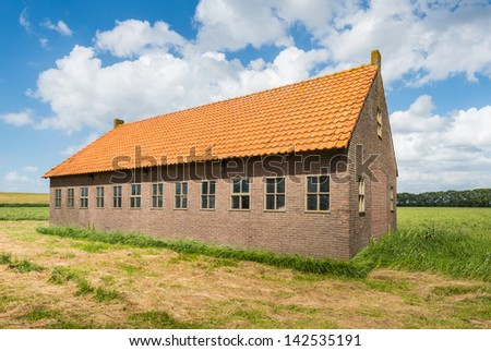Old Dutch barn of brick masonry with an orange tile roof in the summer season.