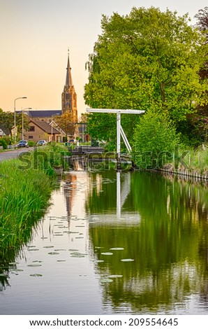 Old Dutch bridge under the big tree, canal and church in the village of Nootdorp, hdr image, focus on bridge and church