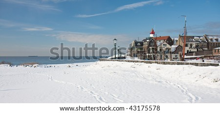 Old dutch fishery village seen in wintertime from the beach - stock photo
