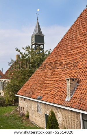 Old dutch historic farmhouse with church tower behind it