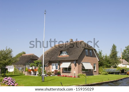 Old dutch house at the waterside - stock photo
