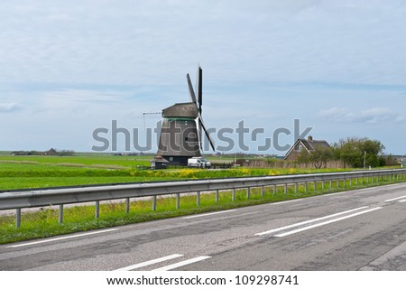 Old Dutch Windmill at the Modern Highway - stock photo