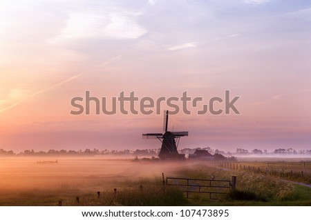 old Dutch windmill in fog in early morning during sunrise - stock photo