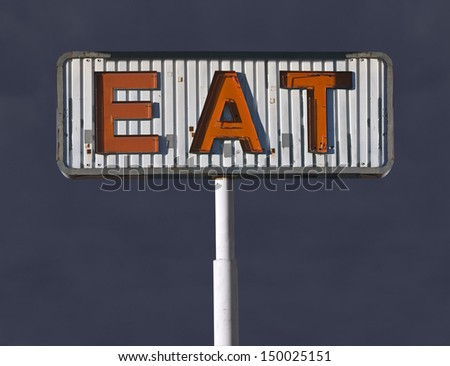 Old eat sign with storm sky. - stock photo