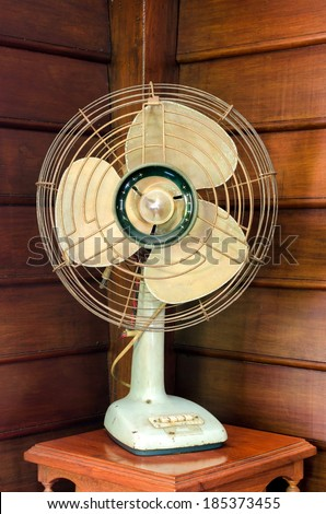 old electric fan on wood table - stock photo