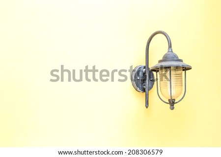 Old electric lamp on yellow wall. - stock photo