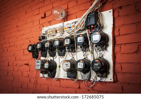 old electric meters on a red brick wall - stock photo