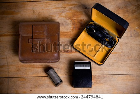 old electric razor on a wooden table. - stock photo