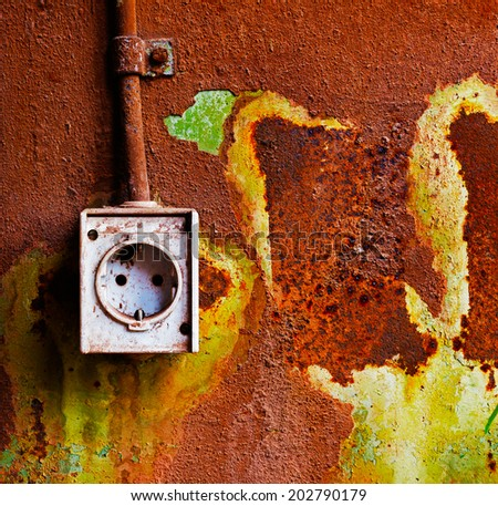 Old electrical outlet on a rusty iron wall - stock photo