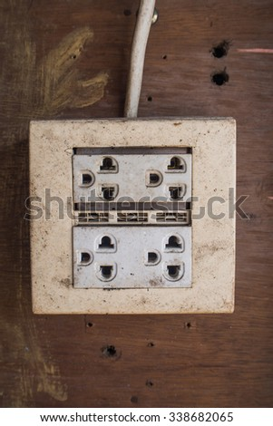 old electrical outlet on wood wall. - stock photo
