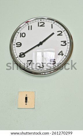 old electrical switch and a modern clock on the wall