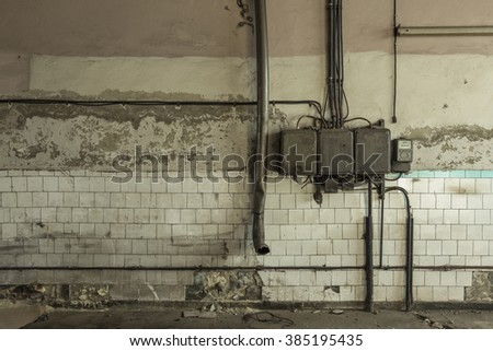 Old electrical wires on grungy wall. Interior in abandoned factory - stock photo