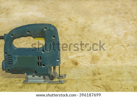 Old electricsaw in working position on the background of OSB. Image with copy space.