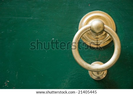 Old elegant golden metal door handle, knocker - stock photo