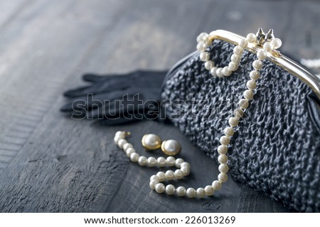 Old elegant vintage handbag from the 1950's with luxury pearls and earrings on black background for copy space - stock photo