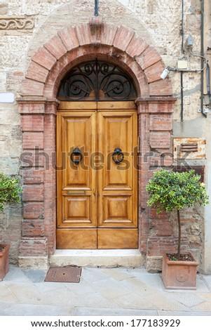 Old elegant wooden door in italian village - stock photo