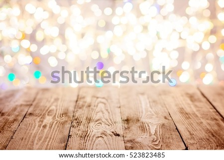 Old empty table with christmas lights in the background . Christmas background
