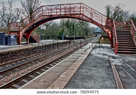 Old English railway station platform bridge and lines - stock photo