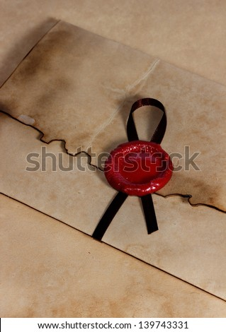 old envelope of ancient parchment paper with a wax seal - stock photo