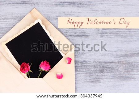 Old envelope with blank photo paper and beautiful pink dried roses on wooden background - stock photo