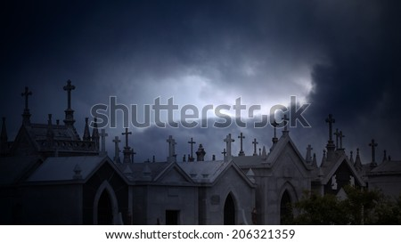 Old european cemetery against dramatic cloudy sky at dusk - stock photo