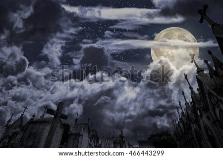 Old european cemetery in a full moon night with many tombs in form of granite chapels with crosses, clouds and stars. Good for halloween backgrounds.Part of the stars were from a a Nasa photo.