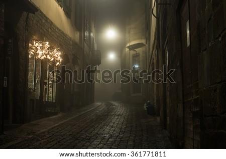 Old European narrow empty street of a medieval town on a foggy evening. Taken in Bergamo, Citta Alta - stock photo