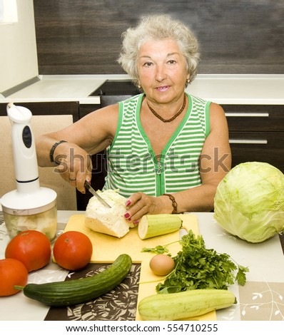 Old European woman in kitchen cooking vegetables.